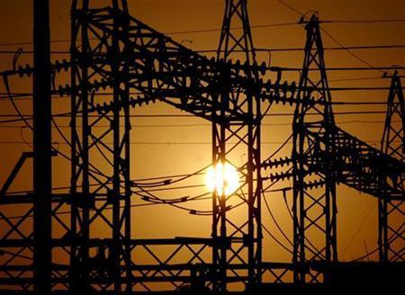 The sun sets behind electric pylons in Allahabad February 22, 2006. REUTERS/Jitendra Prakash/Files