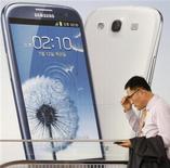 Мужчина проходит мимо рекламы мобильного телефона в магазине Samsung Electronics в Сеуле 27 июля 2012 года. Судебное заседание, которое началось во вторник в американском суде по иску Apple Inc против Samsung Electronics Co Ltd, может стоить миллиарды долларов обеим компаниям. REUTERS/Kim Hong-Ji