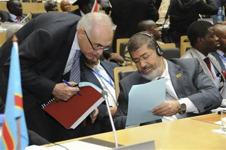 Egypt's President Mohamed Mursi (R) speaks with Egypt's Foreign Minister Mohamed Kamel Amr during the opening of the African Union (AU) leaders' meeting in Addis Ababa July 15, 2012. REUTERS/Egyptian Presidency/Handout