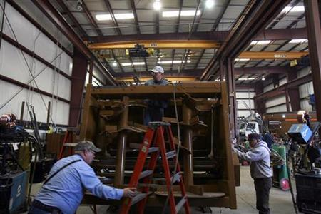 Workers construct a cattle mixer/feeder at a farm equipment manufacturing facility in Merced, California October 27, 2009. REUTERS/Robert Galbraith