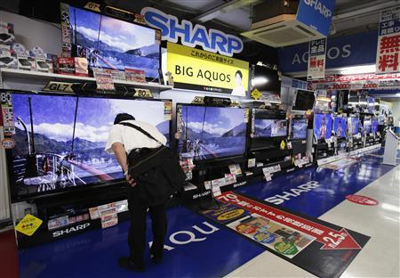 A man looks at Sharp Corp's Aquos TVs displayed at an electronics store in Tokyo August 2, 2012. REUTERS/Yuriko Nakao