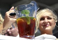 Women drink a traditional Pimm's Cup cocktail as they wait for the start of the second race during Ladies Day at Epsom Racecourse in southern England June 3, 2011. REUTERS/Suzanne Plunkett