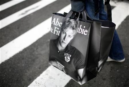 A man holds shopping bags from retailer Abercrombie & Fitch while waiting to cross a street in New York October 8, 2009. REUTERS/Mike Segar/Files