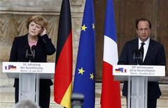 France's President Francois Hollande (R) and German Chancellor Angela Merkel stand at lecterns during the 50th anniversary ceremony of the reconciliation meeting between former French president Charles de Gaulle and German Chancellor Konrad Adenauer after World War Two, in Reims July 8, 2012. REUTERS/Jacky Naegelen