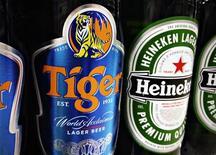 Бутылки пива Tiger и Heineken на полке магазина в Сингапуре, 20 июля 2012 года. Голландский пивной гигант Heineken достиг соглашения с сингапурской Fraser and Neave о покупке ее пакета акций в пивоваренной компании Asia Pacific Breweries за 5,1 миллиарда сингапурских долларов ($4,08 миллиарда). REUTERS/Tim Chong