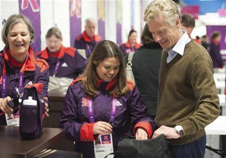 The Chief Executive of the London Organising Committee of the Olympic and Paralympic Games (LOCOG), Paul Deighton, poses for a photograph as he collects his London 2012 Olympic Games uniform at the London 2012 Uniform Distribution and Accreditation Centre in east London April 27, 2012. REUTERS/Ki Price