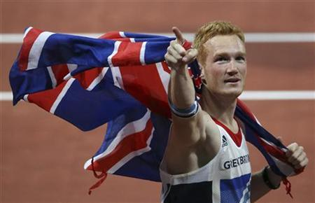 Britain's Greg Rutherford gestures as he holds a Union flag behind him after winning the men's long jump final at the London 2012 Olympic Games at the Olympic Stadium August 4, 2012. Reuters/Stefano Rellandini