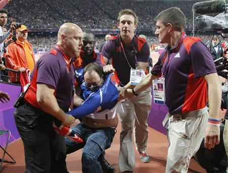 A man is detained by security shortly after an incident during the men's 100 metres final at the London 2012 Olympic Games in London August 5, 2012. REUTERS/Chris Helgren