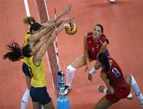 A brasileira Sheilla Castro (à esquerda, embaixo) defende a bola contra a russa Nataliya Goncharova durante as quadras de final de vôlei durante as Olimpíadas de 2012 em Londres, no Reino Unido. 7/08/2012 REUTERS/Ivan Alvaredo