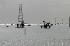 Нефтяные вышки на озере Маракайбо в Венесуэле, 28 февраля 2011 года. Нефть Brent подешевела в среду, отступив от 12-недельного максимума, достигнутого на предыдущей сессии, но опасения о добыче в Северном море и надежды на новые стимулы центробанков удерживают цены выше $111 за баррель. REUTERS/Isaac Urrutia