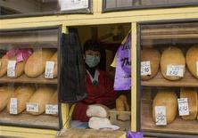 Женщина в защитной маске продает хлеб во Львове 1 ноября 2009 года. Запасы зерна на Украине превышают потребление, и несмотря на сокращение урожая продовольствие не подорожает, сказал премьер-министр Николай Азаров за два с половиной месяца до выборов. REUTERS/Vasily Fedosenko