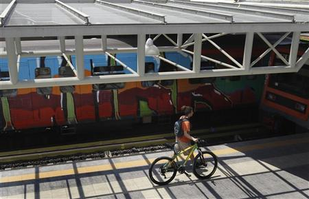 A young man with a bicycle walks inside a city train station in Athens June 26, 2012. REUTERS/John Kolesidis