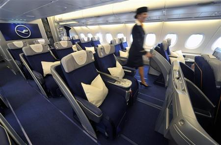 A flight attendant walks past Business Class seats in a new Airbus A380 aircraft for Lufthansa before a hand-over ceremony at the manufacturer's site in Finkenwerder, near Hamburg, May 19, 2010. REUTERS/Morris Mac Matzen
