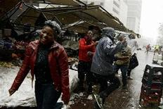 Locals run as an unusual snowfall hits some parts of Johannesburg, August 7, 2012. REUTERS/Stringer