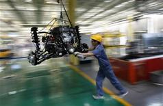 An employee pushes a car engine at a Geely Automobile assembly line in Cixi, Zhejiang province June 21, 2012. REUTERS/Carlos Barria