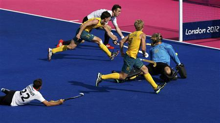 Germany's Matthias Witthaus (L) scores a goal past Australia's goalkeeper Nathan Burgers (R to L), Matthew Butturini and Fergus Kavanagh during their men's semifinal hockey match at the Riverbank Arena at the London 2012 Olympic Games August 9, 2012. REUTERS/Chris Helgren