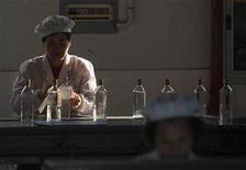 A labourer packages baijiu at the Shanghai Shenxian Rice Winery in Shanghai May 11, 2012. REUTERS/Aly Song