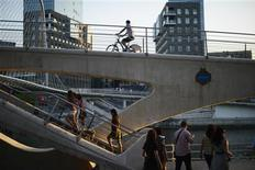 People climb stairs to cross the Zubzuri (White Bridge) pedestrian bridge, designed by Spanish architect Santiago Calatrava, in front of the Torres Isozaki , by Japanese architect Arata Isozaki, at dusk in Bilbao June 26, 2012. REUTERS/Vincent West
