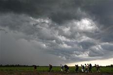 Люди идут под дождевыми облаками на музыкальный фестиваль в Булгаково в 250 км от Москвы, 14 июня 2009 г. Наступающие выходные в Москву обещают стать самыми прохладными днями недели, ожидают синоптики. REUTERS/Denis Sinyakov