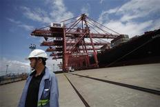 An employee stands next to a container ship at Ningbo port in Ningbo, Zhejiang province June 21, 2012. REUTERS/Carlos Barria