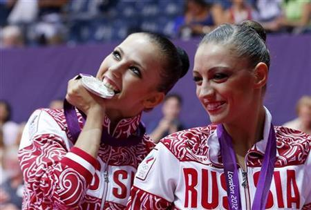 Silver medallist Russia's Daria Dmitrieva (L) celebrates with gold medallist compatriot Evgeniya Kanaeva in the individual all-around gymnastics final victory ceremony at the Wembley Arena during the London 2012 Olympic Games August 11, 2012. REUTERS/Mike Blake