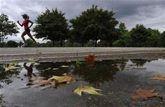 A runner jogs past puddles in Hyde Park in London August 27, 2010. REUTERS/Toby Melville