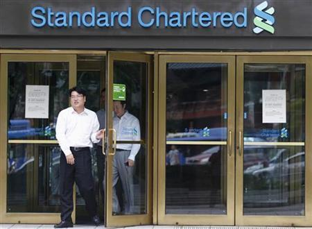 Employees of Standard Chartered leave a branch of the bank in central Seoul August 9, 2012. REUTERS/Lee Jae-Won