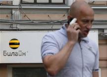 Человек говорит по телефону у офиса Билайн в Москве 28 мая 2012 года. Телекоммуникационная компания Вымпелком во втором квартале 2012 года нарастила чистую прибыль на 83 процента до $488 миллионов по сравнению с $267 миллионами годом ранее, сообщила компания в среду. REUTERS/Maxim Shemetov