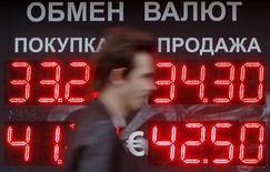 Человек проходит мимо вывески обменного пункта в Москве 4 июня 2012 года. Рубль незначительно подешевел в начале торгов среды, отразив умеренно-отрицательную утреннюю динамику внешних рынков; далее дилеры ждут диапазонной торговли, с реакцией на изменения евро/доллар и нефти, влияние могут оказывать и ордера на покупку/продажу валюты от крупных корпоративных клиентов банков. REUTERS/Denis Sinyakov