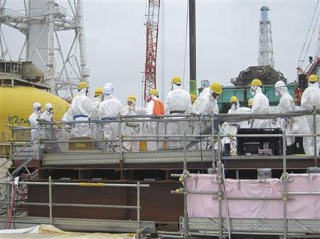 Workers wearing protective suits, work for removing unused nuclear fuel assemblies stored in the spent fuel pool of Tokyo Electric Power Co. (TEPCO)'s tsunami-crippled Fukushima Daiichi Nuclear Power Plant No. 4 reactor building in Fukushima prefecture, in this handout photo taken July 18, 2012, and released by TEPCO July 19, 2012. REUTERS/Tokyo Electric Power Co/Handout