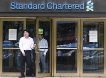 Люди выходят из отделения банка Standard Chartered в Сеуле, 9 августа 2012 года. Банк Standard Chartered пытается заключить коллективное мирное соглашение с властями США после того, как решил заплатить $340 миллионов финансовому регулятору Нью-Йорка под давлением со стороны акционеров. REUTERS/Lee Jae-Won