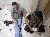 A Free Syrian Army fighter reads the Koran before clashes in Aleppo August 16, 2012. REUTERS/Goran Tomasevic