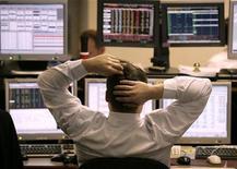 Трейдер Тройки Диалог смотрит на компьютерные мониторы во время утренней торговой сессии в Москве, 20 декабря 2004 года. Торги акциями РФ начались с повышения котировок в пятницу на фоне позитивной динамики рынков США и Азии. REUTERS/Alexander Natruskin
