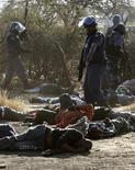 Полицейские на месте расстрела горняков в Рюстенбурге, 16 августа 2012 года. Усиленные наряды южноафриканской полиции патрулируют в пятницу окрестности платинового рудника Марикана компании Lonmin, где накануне были убиты более 30 горняков в столкновениях с полицией, напомнивших местному обществу о временах апартеида. REUTERS/Siphiwe Sibeko