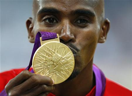 Britain's Mo Farah kisses his gold medal for the men's 5000m at the victory ceremony at the London 2012 Olympic Games at the Olympic Stadium August 11, 2012. REUTERS/Eddie Keogh