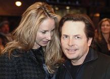 Ator Michael J. Fox (D) e esposa Tracy Pollan chegam na apresentação de Bruce Springsteen durante evento em Nova York. Fox, que reduziu seu ritmo de trabalho em 2000 para se concentrar no combate ao mal de Parkinson, vai estrelar uma nova comédia de televisão baseada em sua própria experiência com a doença. 09/03/2012 REUTERS/Carlo Allegri