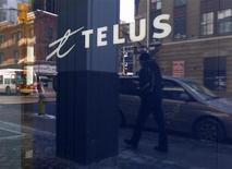 A pedestrian is reflected in the window of a Telus store while using a mobile phone in Ottawa February 11, 2011. Telus said its quarterly profit rose 46 percent, driven largely by strong data and wireless revenue and growth in its landline Internet television service, Optik. REUTERS/Chris Wattie