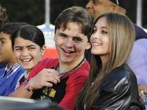 Michael Jackson's children (L-R) Blanket, Prince and Paris share a laugh at a ceremony where the singer is immortalized with hand and foot imprints in cement in the courtyard of Hollywood's Grauman's Chinese Theatre in Los Angeles January 26, 2012. REUTERS/Phil McCarten