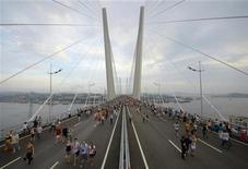 Люди идут по только что открытому мосту через бухту Золотой Рог во Владивостоке 11 августа 2012 года. Кремль вновь украшает витрину на Тихом океане в попытке исправить имидж в глазах инвесторов и поднять популярность у избирателей. REUTERS/Yuri Maltsev