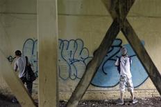 Street artists spray-paint graffiti on a wall under a bridge beside a railway line in Yangon August 25, 2012. REUTERS/Soe Zeya Tun