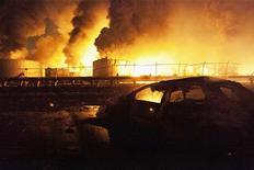 Сгоревшая машина на фоне горящего НПЗ Amuay в Парагуане 25 августа 2012 года. На крупнейшем НПЗ Венесуэлы на выходных произошел взрыв, жертвами которого стал 41 человек. REUTERS/Hector Silva