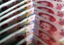 Купюры валюты юань в Пекине 22 марта 2011 года. Промышленный сектор Китая сообщил о резком падении прибылей в июле, ставшем очередным доказательством того что снижение внутреннего и внешнего спроса влияет на корпоративные результаты. REUTERS/Jason Lee
