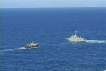 An aerial shot of a vessel from Japan's coast guard (R) blocking the path of a boat carrying Chinese activists who sailed from Hong Kong and landed on the disputed islands known as Senkaku in Japan and Diaoyu in China, in the East China Sea on August 15, 2012 is seen in this still image taken from video released in Tokyo on August 27, 2012. Mandatory Credit REUTERS/11th Regional Coast Guard Headquarters-Japan Coast Guard via Reuters TV/Handout