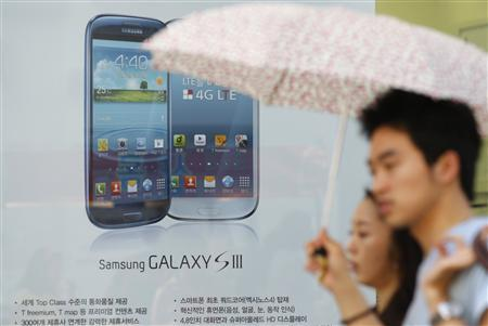 A couple walk past a store selling Samsung Galaxy smartphones in Seoul August 26, 2012. REUTERS/Lee Jae-Won