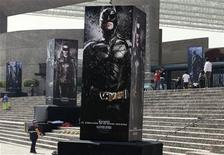 """Posters of the film """"The Dark Knight Rises"""" are displayed outside as people wait for the midnight premiere of the final instalment of Christopher Nolan's Batman trilogy at the National Auditorium in Mexico City July 23, 2012. REUTERS/Henry Romero"""
