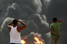 Люди смотрят на горящий НПЗ Amuay в Парагуане 27 августа 2012 года. Пожар на крупнейшем НПЗ Венесуэлы будет потушен в течение двух дней, и предприятие возобновит работу в пятницу, сообщил Рейтер министр энергетики Рафаэль Рамирес. REUTERS/Stringer
