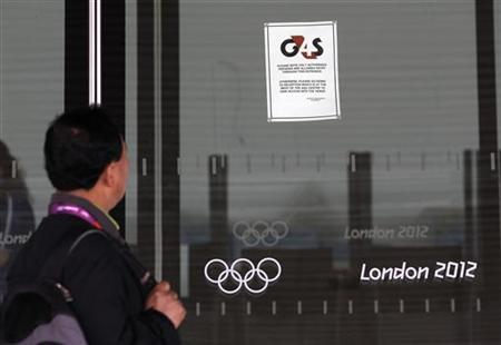 A visitor to the Olympic Park reads a 4GS notice stuck to a window at the Aquatics centre, in the Olympic Park, in Stratford, east London, July 17, 2012. REUTERS/Andrew Winning