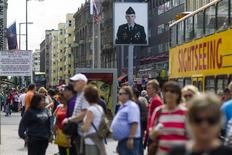 Tourists walk near the former Checkpoint Charlie border crossing in Berlin, August 25, 2012. More than two decades after the fall of the Berlin Wall, differences over how to represent the Cold War past are hampering plans to build a new museum at the former border crossing. Picture taken August 25, 2012. REUTERS/Thomas Peter