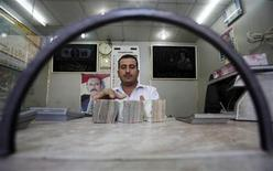 A money exchanger counts stacks of Yemeni rials in his shop in Sanaa January 5, 2011. REUTERS/Khaled Abdullah