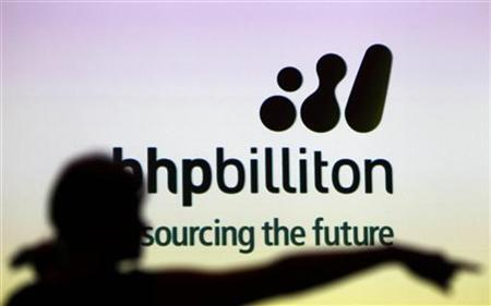 A woman gestures in front of a BHP Billiton sign during a half-year results briefing by the company's Chief Executive Marius Kloppers, in central Sydney February 16, 2011. REUTERS/Tim Wimborne